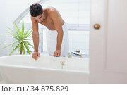 Handsome man in towel leaning over bath. Стоковое фото, агентство Wavebreak Media / Фотобанк Лори