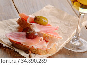 Open jamon sandwiches with white wine on wooden table. Стоковое фото, фотограф Olena Mykhaylova / easy Fotostock / Фотобанк Лори