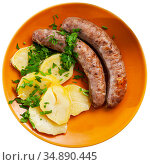 Fried sausages served with baked potatoes and greens. Стоковое фото, фотограф Яков Филимонов / Фотобанк Лори