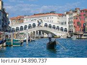 Гондольер на гондоле на фоне моста Риальто солнечным днем. Венеция (2017 год). Редакционное фото, фотограф Виктор Карасев / Фотобанк Лори