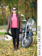 Female motorcycle rider standing next to a motorbike, woman holding helmet in hand. Full-length portrait in autumn park. Стоковое фото, фотограф Кекяляйнен Андрей / Фотобанк Лори