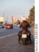 Rear view at motorbiker with motorcycle standing on urban road, female rider is ready to start movement in city. Стоковое фото, фотограф Кекяляйнен Андрей / Фотобанк Лори