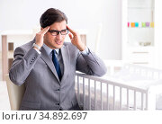 Young businessman trying to work from home caring after newborn. Стоковое фото, фотограф Elnur / Фотобанк Лори