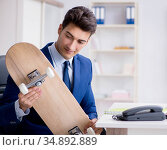Young businessman with skate in office in sports concept. Стоковое фото, фотограф Elnur / Фотобанк Лори