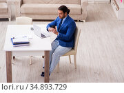 Young male employee working from house in self-isolation concept. Стоковое фото, фотограф Elnur / Фотобанк Лори