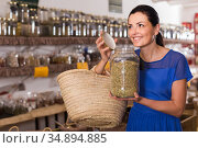 adult female take a smell natural dried herbs sold by weight in eco shop. Стоковое фото, фотограф Яков Филимонов / Фотобанк Лори