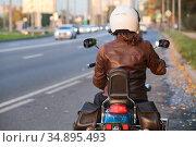 Young woman getting ready for motorcycle ride, sitting on bike, rear view, urban road. Стоковое фото, фотограф Кекяляйнен Андрей / Фотобанк Лори