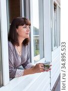 Adult woman in the morning holding a cup of tea or coffee and looking away standing near the window in her home. Стоковое фото, фотограф Кекяляйнен Андрей / Фотобанк Лори
