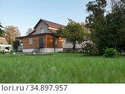 Low country house with backyard, green lawn, nobody. Стоковое фото, фотограф Кекяляйнен Андрей / Фотобанк Лори