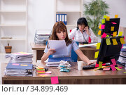 Two female employees and excessive work in the office. Стоковое фото, фотограф Elnur / Фотобанк Лори