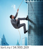 Businessman climbing skyscraper in challenge concept. Стоковое фото, фотограф Elnur / Фотобанк Лори