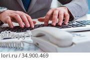 Finance professional working on keyboard with reports. Стоковое фото, фотограф Elnur / Фотобанк Лори