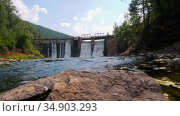 Water dam in the middle of the forest - water falls down under the bridge in shallow water. Стоковое видео, видеограф Константин Шишкин / Фотобанк Лори