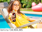 Young long hair girl give soda glass bottle. Стоковое фото, фотограф Сергей Новиков / Фотобанк Лори