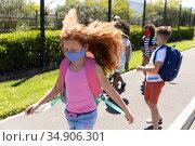 Group of kids wearing face masks walking on footpath. Стоковое фото, агентство Wavebreak Media / Фотобанк Лори