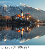 Church of the Assumption and mountains reflected in Lake Bled. Upper Carniola, Slovenia. February 2020. Стоковое фото, фотограф Guy Edwardes / Nature Picture Library / Фотобанк Лори