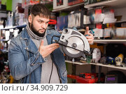 Hardware store visitor chooses circular saw in tool store. Стоковое фото, фотограф Яков Филимонов / Фотобанк Лори