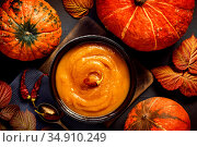 Healthy natural vegetarian food for thanksgiving day, pumpkin puree soup hot with chili spices, chutney homemade vegetable caviar in a plate with fruits, autumn still life flat lay on black background. Стоковое фото, фотограф Светлана Евграфова / Фотобанк Лори