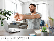 man with laptop stretching at home office. Стоковое фото, фотограф Syda Productions / Фотобанк Лори