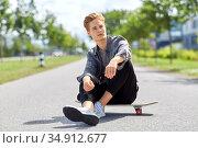 teenage boy sitting on skateboard on city street. Стоковое фото, фотограф Syda Productions / Фотобанк Лори