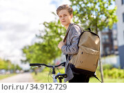 young man with bicycle and backpack on city street. Стоковое фото, фотограф Syda Productions / Фотобанк Лори