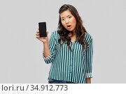 shocked asian woman over grey background. Стоковое фото, фотограф Syda Productions / Фотобанк Лори