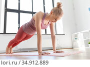 young woman doing plank exercise on mat at home. Стоковое фото, фотограф Syda Productions / Фотобанк Лори