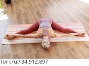 young woman doing full split on mat at home. Стоковое фото, фотограф Syda Productions / Фотобанк Лори