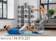 happy young man and woman exercising at home. Стоковое фото, фотограф Syda Productions / Фотобанк Лори
