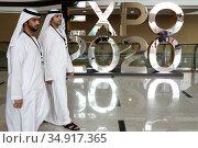 Dubai, United Arab Emirates, men in national costume walk past an advertising display for Expo 2020 (2019 год). Редакционное фото, агентство Caro Photoagency / Фотобанк Лори
