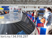 People are waiting for luggage in airport terminal without keeping a social distance. Notice boards asking them to keep a social distance. Antalya, Turkey. Редакционное фото, фотограф Кекяляйнен Андрей / Фотобанк Лори