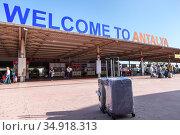 Antalya, Turkey-circa Oct, 2020: Two luggages stand against signboard of the Antalya International airport. Inscription the Welcome to Antalya is in arrival terminal. Редакционное фото, фотограф Кекяляйнен Андрей / Фотобанк Лори