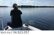 Teenager girl sits on bow of fast moving motorboat, speedboat floating on lake water surface, copyspace. Стоковое видео, видеограф Кекяляйнен Андрей / Фотобанк Лори