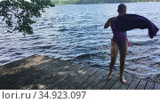 Caucasian teenage girl gets out from the water on wooden pier and wipes with towel, forest lake at summer season. Стоковое видео, видеограф Кекяляйнен Андрей / Фотобанк Лори