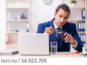 Young male employee and a lot of pills on the desk. Стоковое фото, фотограф Elnur / Фотобанк Лори