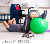 Young male employee exercising in the office. Стоковое фото, фотограф Elnur / Фотобанк Лори