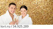 happy couple in spa bath robes drinking champagne. Стоковое фото, фотограф Syda Productions / Фотобанк Лори