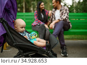 Happy parents with little baby leisures on bench. Стоковое фото, фотограф Tryapitsyn Sergiy / Фотобанк Лори