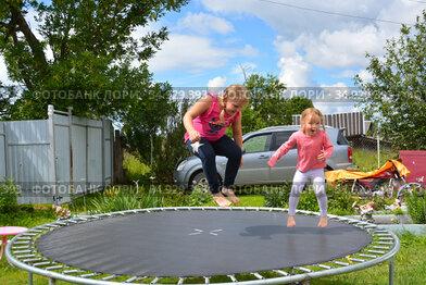 В жаркий солнечный день дети прыгают на батуте