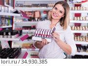 smiling young woman choosing stylish lipstick at store. Стоковое фото, фотограф Яков Филимонов / Фотобанк Лори