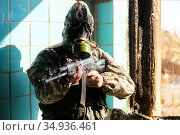 military man in a gas mask, hooded, aiming to point his weapon at the camera. Стоковое фото, фотограф Владимир Арсентьев / Фотобанк Лори