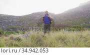 Senior hiker man with backpack standing on the grass field in the mountains. trekking. Стоковое видео, агентство Wavebreak Media / Фотобанк Лори