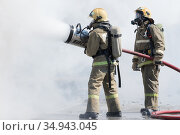 Two firefighters extinguish fire from fire hose, using firefighting water-foam barrel with air-mechanical foam (2019 год). Редакционное фото, фотограф А. А. Пирагис / Фотобанк Лори