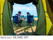 married couple drinking tea while sitting in chairs near the camping by the sea. Стоковое фото, фотограф Константин Лабунский / Фотобанк Лори