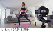 Woman performing exercise at home and recording it with digital camera. Стоковое видео, агентство Wavebreak Media / Фотобанк Лори