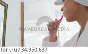 Woman in bathrobe brushing teeth while looking in the mirror. Стоковое видео, агентство Wavebreak Media / Фотобанк Лори