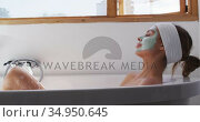 Woman wearing face pack relaxing in bathtub. Стоковое видео, агентство Wavebreak Media / Фотобанк Лори