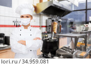 female chef in mask with crossed arms at kitchen. Стоковое фото, фотограф Syda Productions / Фотобанк Лори
