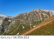 Sunny high-mountain slopes with alpine meadows and strips of geological layers - spurs of Mount Fisht in the Caucasus. Стоковое фото, фотограф Евгений Харитонов / Фотобанк Лори