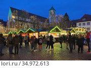 Фрайбург, Германия. Рождественский базар на Ратушной площади около церкви св. Мартина вечером (2019 год). Редакционное фото, фотограф Михаил Марковский / Фотобанк Лори